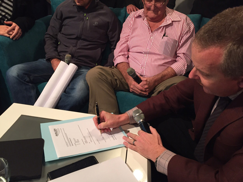 Ps Andre Roebert signs the construction agreement with Avalon Steel Projects during a live television broadcast