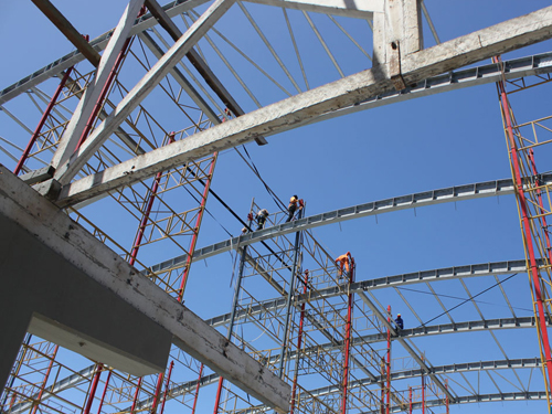 Construction workers scattered like acrobats  across the steel girders